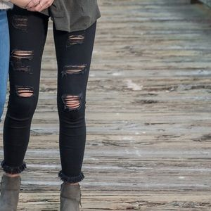 Distressed black jeggings with frayed bottoms